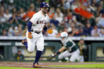Houston Astros second baseman Jose Altuve, left, hustles to first base as Oakland Athletics catcher Aramis Garcia, right, prepares to throw to first base for the out during the third inning of a baseball game Thursday, July 8, 2021, in Houston. (AP Photo/Michael Wyke)