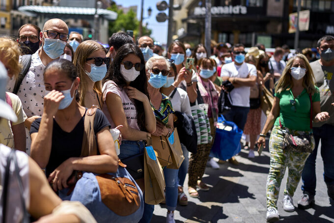 People wearing face masks stand along a street in Madrid, Spain, Thursday, June 24, 2021. Spain is easing its COVID-19 pandemic rules, permitting people to stop wearing masks outdoors and allowing sports fans back into stadiums.  Almost a year after face masks became mandatory indoors and outdoors, people from Saturday will no longer be required to wear them outside as long as they can stay at least 1.5 meters (5 feet) apart. (AP Photo/Manu Fernandez)