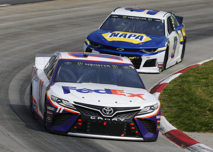 NASCAR Cup Series driver Denny Hamlin (11) leads Chase Elliott (9) into turn four during the NASCAR Cup Series auto race at the Martinsville Speedway in Martinsville, Va., Sunday, March 24, 2019. (AP Photo/Steve Helber)