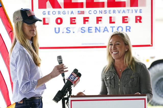 Republican congressional candidate Marjorie Taylor Greene, right, introduces Sen. Kelly Loeffler, R-Ga., left, during a news conference on Thursday, Oct. 15, 2020, in Dallas, Ga. (AP Photo/Brynn Anderson)