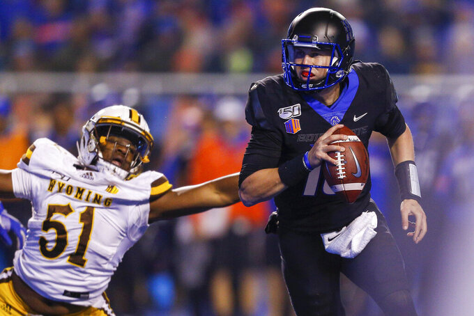 Boise State quarterback Chase Cord (10) runs just out of reach of Wyoming defensive end Solomon Byrd (51) during the second half of an NCAA college football game Saturday, Nov. 9, 2019, in Boise, Idaho. Boise State won 20-17. (AP Photo/Steve Conner)