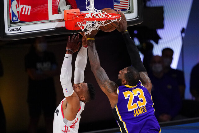 Los Angeles Lakers' LeBron James (23) blocks a shot by Houston Rockets' Russell Westbrook (0) during the second half of an NBA conference semifinal playoff basketball game Friday, Sept. 4, 2020, in Lake Buena Vista, Fla. (AP Photo/Mark J. Terrill)