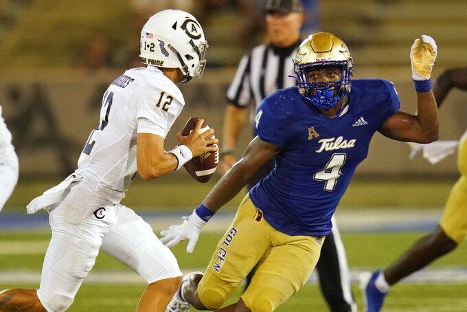 UC Davis quarterback Hunter Rodrigues (12) is pressured by Tulsa linebacker Robert Revels III (4) fduring the second half of an NCAA college football game Thursday, Sept. 2, 2021, in Tulsa, Okla. (AP Photo/Sue Ogrocki)