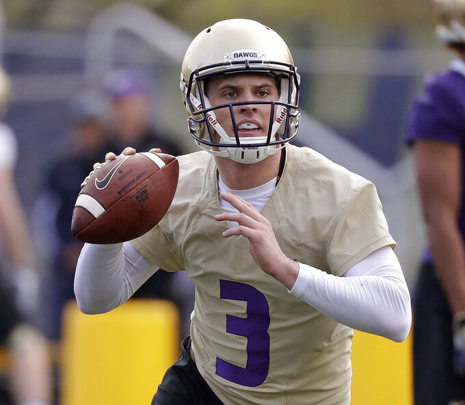 FILE - In this March 28, 2018, file photo, Washington quarterback Jake Browning looks to pass during an NCAA college football practice, in Seattle. Potential Heisman Trophy contender Browning will lead No. 6 Washington against No. 9 Auburn in the only opening-week game between top-10 teams. (AP Photo/Elaine Thompson, File)