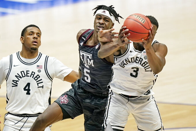 Texas A&M's Emanuel Miller (5) reaches for a rebound with Vanderbilt's Maxwell Evans (3) in the second half of an NCAA college basketball game in the Southeastern Conference Tournament Wednesday, March 10, 2021, in Nashville, Tenn. (AP Photo/Mark Humphrey)