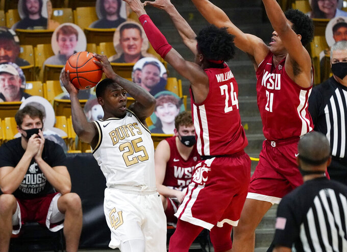 Colorado guard McKinley Wright IV, left, is defended by Washington State guard Noah Williams and center Dishon Jackson during the first half of an NCAA college basketball game Wednesday, Jan. 27, 2021, in Boulder, Colo. (AP Photo/David Zalubowski)