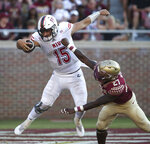FILE - In this Saturday, Sept. 22, 2018, file photo, Northern Illinois' Marcus Childers scores a touchdown as he breaks the tackle of Florida State's Zaquandre White during an NCAA college football game, in Tallahassee Fla. The road trip to Tallahassee came with a $1.6 million payout to NIU. (AP Photo/Steve Cannon, File)
