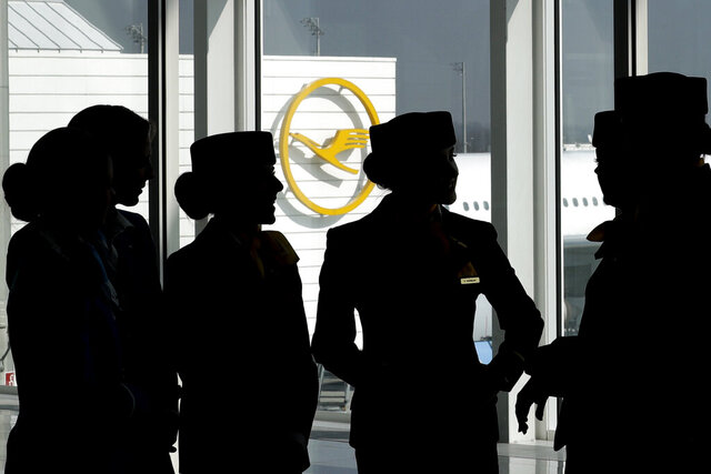 FILE - In this Thursday, March 16, 2017 file photo Lufthansa flight attendants silhouetted as they pose for a photograph on occasion of the company's annual press conference in Munich, Germany. Germany's Lufthansa and a union representing cabin crew said Friday that they have agreed on a wide-ranging arbitration process to resolve a bitter long-running dispute, staving off any further strikes for the time being. (AP Photo/Matthias Schrader, file)