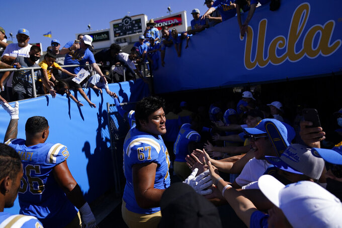 UCLA offensive lineman Yutaka Mahe (67) greets fans as he leaves the field after an NCAA college football game against Hawaii Saturday, Aug. 28, 2021, in Pasadena, Calif. UCLA won 44-10. (AP Photo/Ashley Landis)