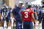 FILE - In this July 28, 2021, file photo, Seattle Seahawks offensive coordinator Shane Waldron, left, talks with quarterback Russell Wilson during NFL football practice in Renton, Wash.  Of all the offseason moves made by the Seattle Seahawks none may end up being more important than hiring Waldron as offensive coordinator. Tasked with modernizing Seattle's offense and making Russell Wilson happy, Waldron's system finally gets its unveiling in the opener on Sunday against Indianapolis.(AP Photo/Ted S. Warren, File)