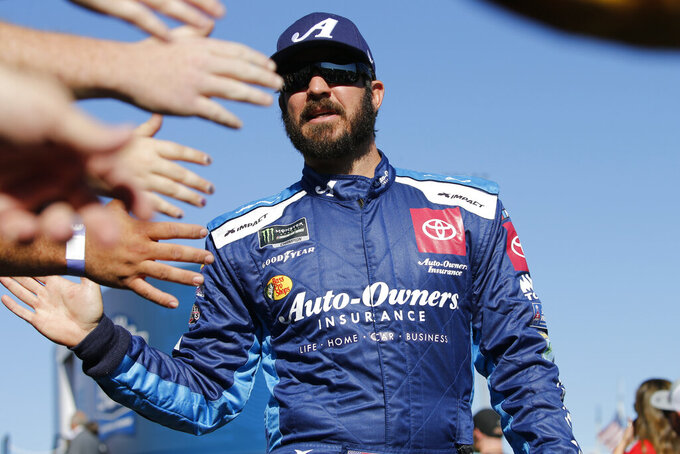 Martin Truex Jr. greets fans during a NASCAR Cup Series race at Martinsville Speedway in Martinsville, Va., Sunday, Oct. 27, 2019. (AP Photo/Steve Helber)