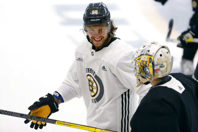 Boston Bruins right wing David Pastrnak jokes with goalie Daniel Vladar as they skate to the bench at the NHL hockey team's camp on Wednesday, July 15, 2020, in Boston. (AP Photo/Charles Krupa)