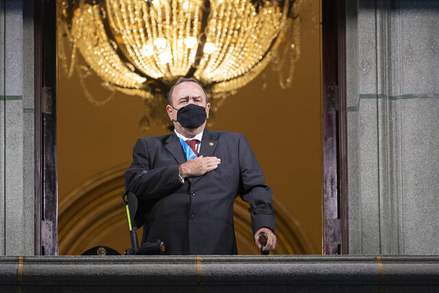 Guatemalan President Alejandro Giammattei wearing a protective face mask as a precaution against the spread of the new coronavirus sings the national anthem during the independence day celebration in Guatemala City, Monday, Sept. 14, 2020. Guatemala and Central America are celebrating 199 years of independence from Spain. (AP Photo/Moises Castillo)