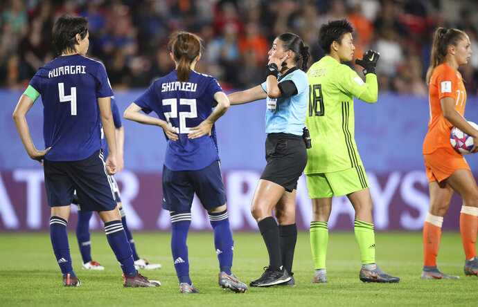 Referee Melissa Borjas, center, consults with VAR after awarding a penalty to the Dutch team during the Women's World Cup round of 16 soccer match between the Netherlands and Japan at the Roazhon Park, in Rennes, France, Tuesday, June 25, 2019. Lieke Martens scored from the spot and the Netherlands won the match 2-1. (AP Photo/David Vincent)