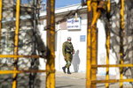 An Israeli soldier walks past a sign reads Israeli Police Rosh Hanikra point in the Rosh Hanikra border crossing between Israel and Lebanon in northern Israel, Wednesday, Oct. 14, 2020. Lebanon and Israel began indirect talks Wednesday over their disputed maritime border, with American officials mediating the talks that both sides insist are purely technical and not a sign of any normalization of ties. (AP Photo/Ariel Schalit)