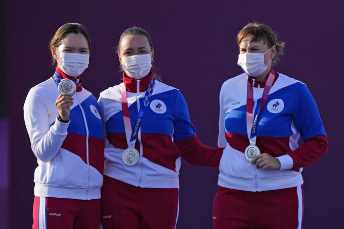 From left, second placed Svetlana Gomboleva, Elena Osipova, and Ksenia Perova, of the Russian Olympic Committee celebrate on the podium of the women's team competition at the 2020 Summer Olympics, Sunday, July 25, 2021, in Tokyo, Japan. (AP Photo/Alessandra Tarantino)
