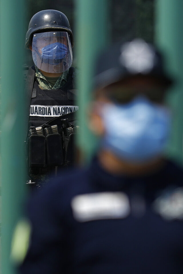 A member of the National Guard stands watch inside the gates as state police guard the street outside, at Las Americas General Hospital in Ecatepec, a suburb of Mexico City, Wednesday, May 20, 2020. Mexico City, one of the world's largest cities and the epicenter of the country's coronavirus epidemic, will begin a gradual reopening June 1, its mayor said Wednesday, even as daily new infections continued to set records. (AP Photo/Rebecca Blackwell)