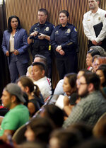 Phoenix police officers stand along the wall as protesters angered by a video of Phoenix officers who pointed guns and yelled obscenities at a black family they suspected of shoplifting gather inside City Council chambers, Wednesday, June 19, 2019, in Phoenix to demand reforms. Speakers called on the council to fire the officers involved in the videotaped incident and to create a board of civilians to oversee changes in department procedures. (AP Photo/Matt York)