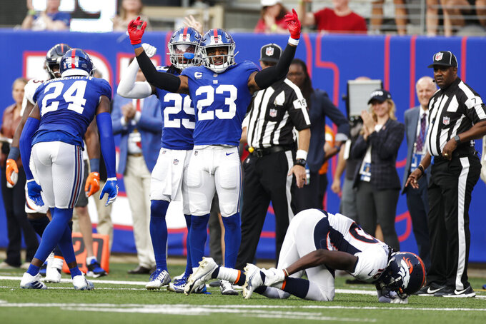 Denver Broncos wide receiver Jerry Jeudy (10) reacts after he was injured on a play after he was tackled by New York Giants' Logan Ryan (23) and James Bradberry (24) during the second half of an NFL football game Sunday, Sept. 12, 2021, in East Rutherford, N.J. (AP Photo/Adam Hunger)