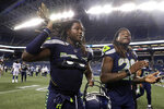 "FILE - In this Thursday, Aug. 9, 2018, file photo, Seattle Seahawks linebacker Shaquem Griffin, left, and his twin brother, cornerback Shaquill Griffin, leave the field following the team's NFL football preseason game against the Indianapolis Colts, in Seattle. The NFL is partnering with three non-profit, non-partisan organizations to get out the vote as the league leverages its ""Inspire Change"" initiative. The program will support and encourage voting and civic engagement efforts of current and former NFL players, club and league personnel and fans beginning Friday, Aug. 7, 2020, until Election Day in November. The Griffins are at the forefront of the movement among players. (AP Photo/Stephen Brashear, File)"