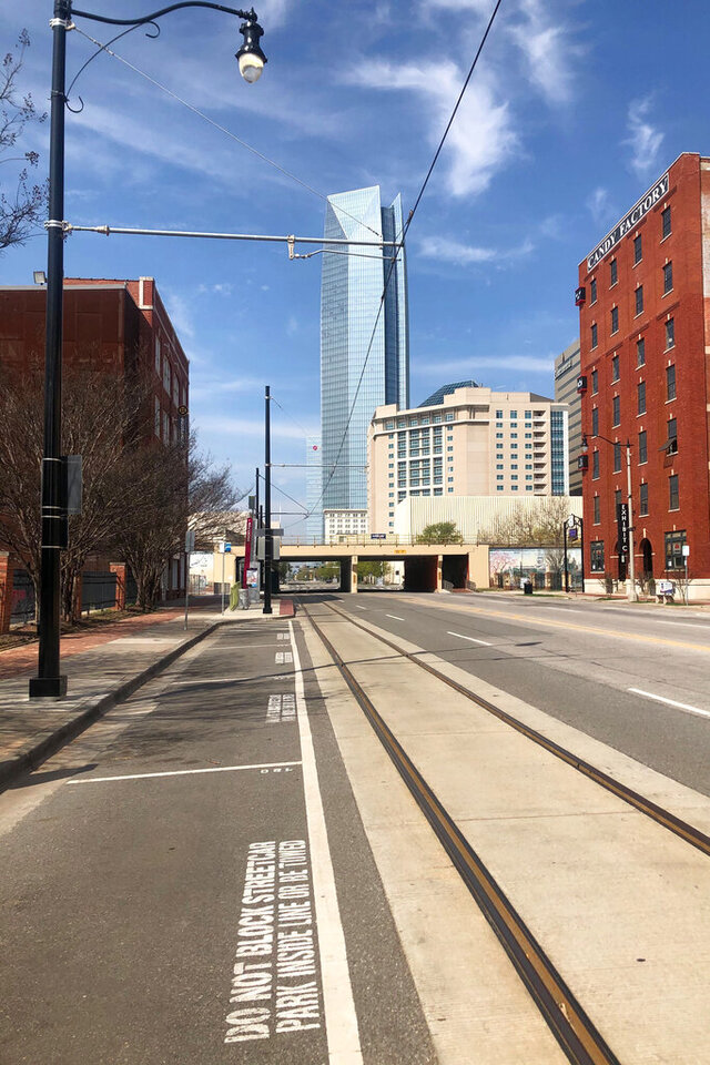 The Devon Energy Center, the tallest building in Oklahoma, towers over empty parking spaces and a barren Sheridan Avenue where businesses are largely closed in the normally vibrant Bricktown section of Oklahoma City, Friday, March 27, 2020. (AP Photo/Cliff Brunt)