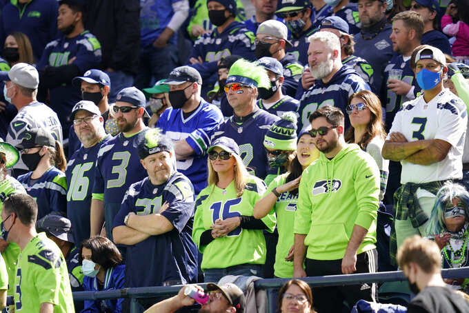 Fans in the stands at Lumen Field are mostly mask-less despite a stadium requirement for them to be worn due to the COVID-19 pandemic, at the start of an NFL football game between the Seattle Seahawks and the Tennessee Titans, Sunday, Sept. 19, 2021, in Seattle. (AP Photo/Elaine Thompson)
