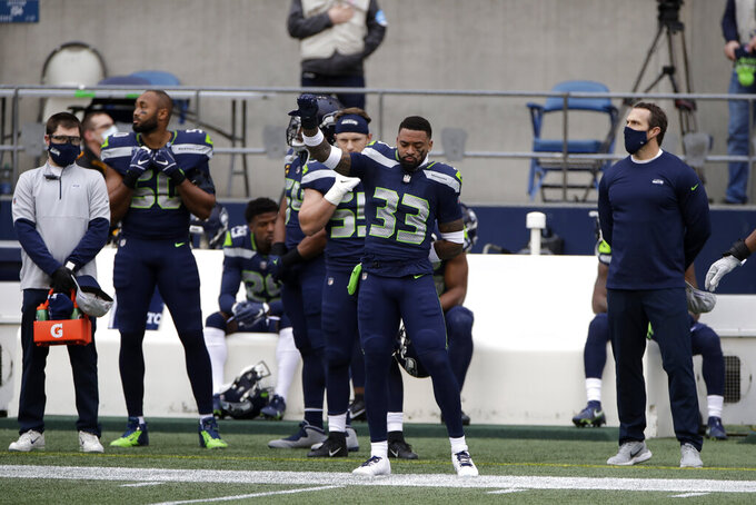 Seattle Seahawks running back Dion Lewis (33) stands with his fist in the air during the national anthem before an NFL football game against the New York Giants, Sunday, Dec. 6, 2020, in Seattle. (AP Photo/Larry Maurer)