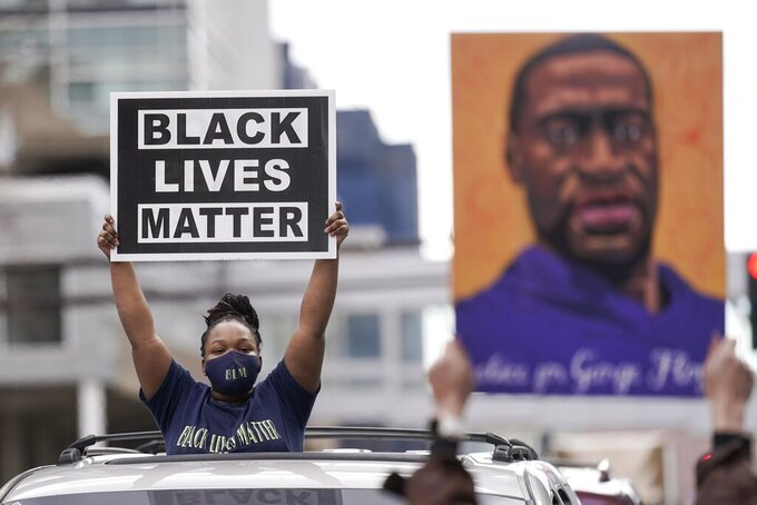 People hold signs, including one with an image of George Floyd, outside the courthouse in Minneapolis on Tuesday, April 20, 2021, after the guilty verdicts were announced in the murder trial of former Minneapolis police Officer Derek Chauvin in the death of Floyd. (AP Photo/Morry Gash)