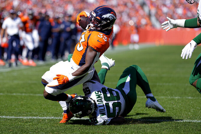 Denver Broncos running back Javonte Williams (33) scores a touchdown as New York Jets outside linebacker Quincy Williams (56) makes the tackle during the first half of an NFL football game, Sunday, Sept. 26, 2021, in Denver. (AP Photo/Jack Dempsey)