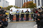 Protesters stand in front of an image of North Korea's Diamond Mountain as they stage a rally calling for the resumption of Diamond Mountain tourism in Seoul, South Korea, Monday, Oct. 28, 2019. South Korea on Monday proposed a face-to-face meeting with North Korea on the fate of a long-shuttered joint tourist project at a scenic North Korean mountain, as their relations remain cool over stalemated nuclear diplomacy. (AP Photo/Ahn Young-joon)