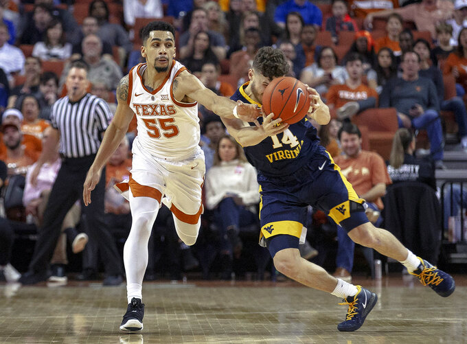Texas guard Elijah Mitrou-Long (55) and West Virginia guard Chase Harler (14) battle for possession of the ball during an NCAA college basketball game on Saturday, Jan. 5, 2019, in Austin, Texas. (Nick Wagner/Austin American-Statesman via AP)
