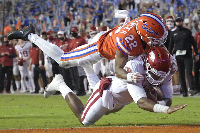 Arkansas quarterback KJ Jefferson rushes for a 12-yard touchdown as Florida defensive back Rashad Torrence II (22) goes for the tackle during the second half of an NCAA college football game Saturday, Nov. 14, 2020, in Gainesville, Fla. (AP Photo/Phelan M. Ebenhack)