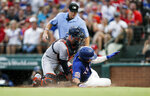 Houston Astros catcher Max Stassi, front left, is unable to hold onto the ball as Texas Rangers' Shin-Soo Choo, front right, scores on a sacrifice fly hit by Nomar Mazara during the third inning of a baseball game, Saturday, July 13, 2019, in Arlington, Texas. (AP Photo/Brandon Wade)