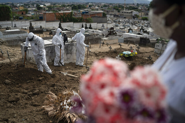 Cemetery workers wearing hazmat suits complete the burial of Ana Maria, a 56-year-old nursing assistantwho died from the new coronavirus, in Rio de Janeiro, Brazil, Tuesday, April 28, 2020. Ana Maria's daughter Taina dos Santos said that the situation in the Salgado Filho public hospital where her mother worked is complicated and that some health workers have to buy their own protective gear.