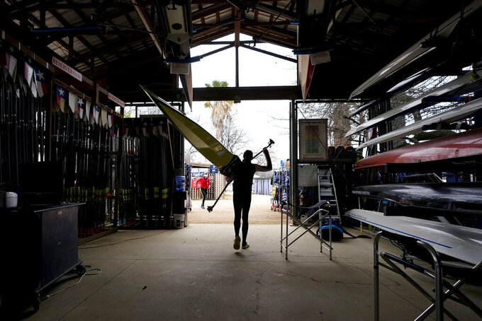 Rower Gevvie Stone carries her board before training at Lady Bird Lake ahead of the upcoming U.S. Olympic rowing trials, Friday, Feb. 12, 2021, in Austin, Texas. (AP Photo/Eric Gay)
