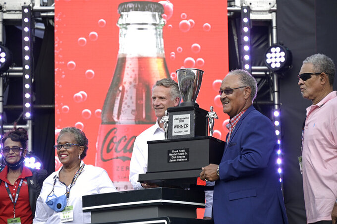 NASCAR President Steve Phelps, center, presents a trophy to Wendell Scott's son Frank Scott before a NASCAR Cup Series auto race at Daytona International Speedway, Saturday, Aug. 28, 2021, in Daytona Beach, Fla. NASCAR presented Scott's family a custom trophy commemorating his historic 1963 victory. Scott was the only Black driver to win a race at NASCAR's top level. (AP Photo/Phelan M. Ebenhack)