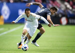 FILE - In this April 13, 2018, file photo, Los Angeles FC's Marco Urena, front, moves the ball past Vancouver Whitecaps' Jose Aja during the first half of an MLS soccer match in Vancouver, British Columbia. Urena was selected for Cost Rica's 23-man roster for the World Cup in Russia. (Darryl Dyck/The Canadian Press via AP, File)