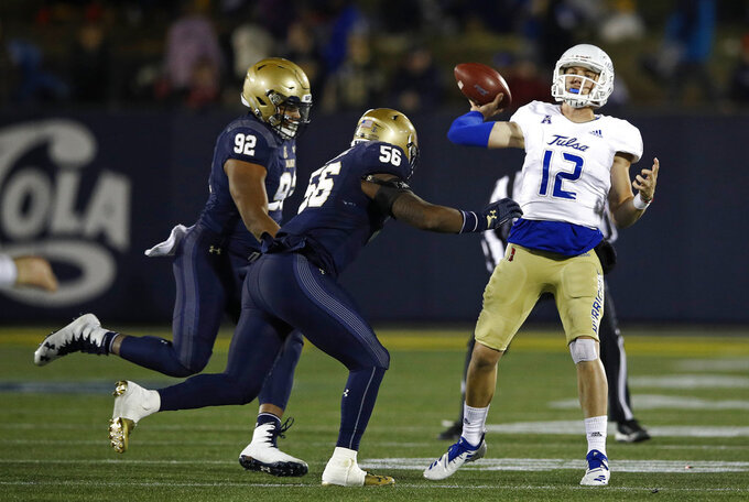 Tulsa quarterback Seth Boomer, right, throws a pass as he is pressured by Navy defensive end Josh Webb (92) and linebacker Nizaire Cromartie in the second half of an NCAA college football game, Saturday, Nov. 17, 2018, in Annapolis, Md. (AP Photo/Patrick Semansky)