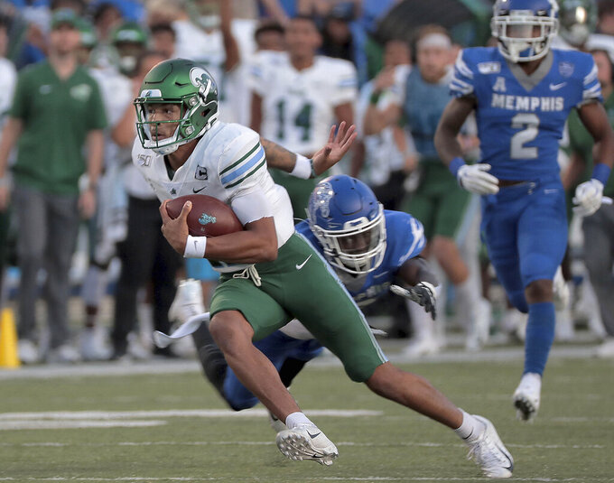 Tulane quarterback Justin McMillan dodges a Memphis tackler during an NCAA college football game Saturday, Oct. 19, 2019, in Memphis, Tenn. (Jim Weber/Daily Memphian via AP)