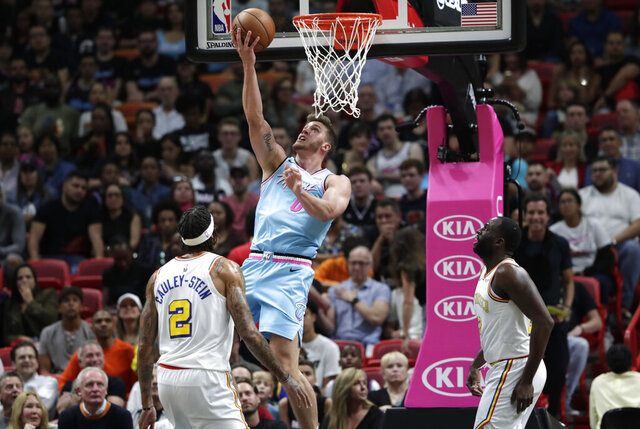 Miami Heat forward Meyers Leonard (0) shoots over Golden State Warriors center Willie Cauley-Stein (2) and forward Draymond Green, right, during the first half of an NBA basketball game, Friday, Nov. 29, 2019, in Miami. (AP Photo/Lynne Sladky)