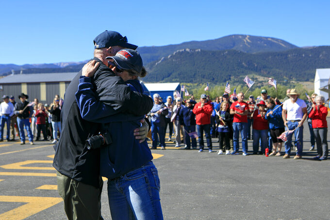 Red Lodge firefighter Dan Steffensen, 65, left, hugs Amy Hyfield as he gets off his airplane during his return home Tuesday, Sept. 21, 2021, at the Red Lodge Airport in Red Lodge, Mont. Steffensen was flown to the University of Utah Burn Center in July after being severely burned while fighting a fire north of Joliet, Mont. (Ryan Berry/The Billings Gazette via AP)