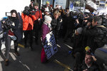 Climate activist Greta Thunberg, center, leaves a media event the congress center where the World Economic Forum take place in Davos, Switzerland, Friday, Jan. 25, 2019. The poster reads: 'School strike for the climate'. (AP Photo/Markus Schreiber)