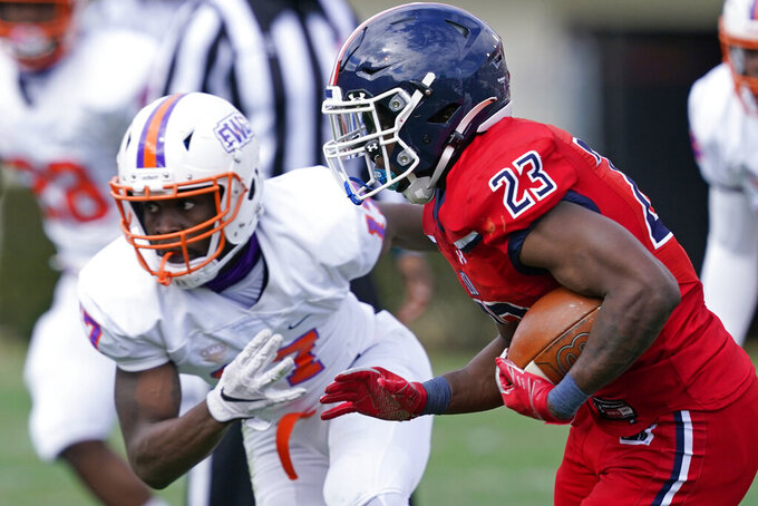 Jackson State running back Kymani Clarke (23) runs past an Edward Waters defender during the first half of an NCAA college football game in Jackson, Miss., Sunday, Feb. 21, 2021. The game marks Sanders's collegiate head coaching debut. (AP Photo/Rogelio V. Solis)