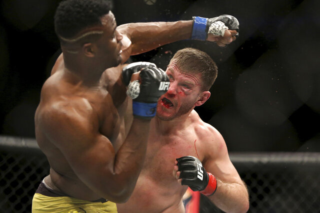 FILE - In this Jan. 21, 2018, file photo, Stipe Miocic, right, lands a right hand against Francis Ngannou during a heavyweight championship mixed martial arts bout at UFC 220 in Boston. Heavyweight champion Stipe Miocic welcomes the UFC's planned return. The fighter and firefighter does have some worries, though. (AP Photo/Gregory Payan, File)