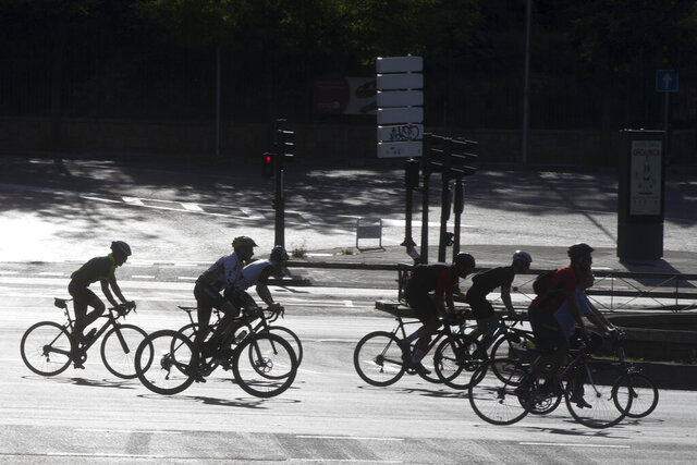 In this photo taken on Sunday May 3, 2020, a group of cyclists, many on racing bikes, ride down the Paseo de la Castellana boulevard in Madrid, Spain after Spaniards were able to go outdoors to do exercise for the second time in seven weeks since the lockdown began to battle the coronavirus outbreak. High-performance athletes were allowed to resume training this week but some reported being harassed by local residents who thought they were breaking confinement rules. (AP Photo/Paul White)