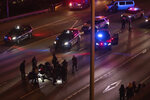 Rescatistas atienden a una mujer herida en el suelo después de que un conductor arremetió con su auto contra las personas que bloqueaban una autopista durante una protesta en Seattle, la madrugada del sábado 4 de julio de 2020. (James Anderson vía AP)