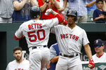 Boston Red Sox's Xander Bogaerts, right, greets teammate Mookie Betts after Betts rounded the bases on a solo home run in the third inning of a baseball game against the Baltimore Orioles, Wednesday, June 13, 2018, in Baltimore. (AP Photo/Patrick Semansky)