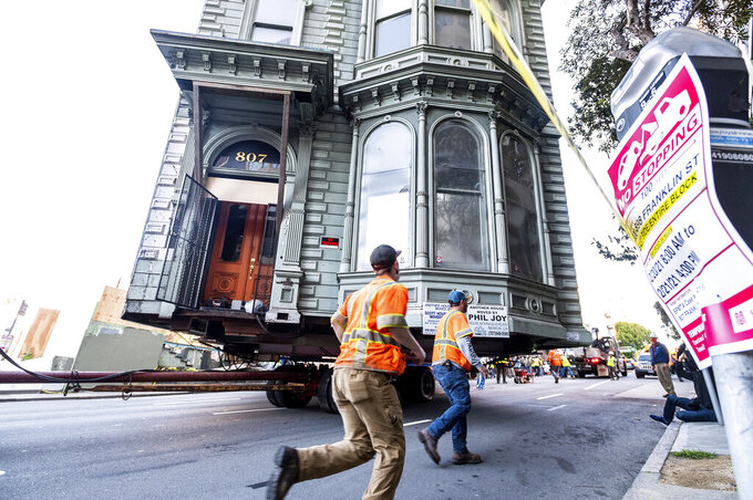 Workers pass a Victorian home as a truck pulls it through San Francisco on Sunday, Feb. 21, 2021. The house, built in 1882, was moved to a new location about six blocks away to make room for a condominium development. According to the consultant overseeing the project, the move cost approximately $200,000 and involved removing street lights, parking meters, and utility lines. (AP Photo/Noah Berger)