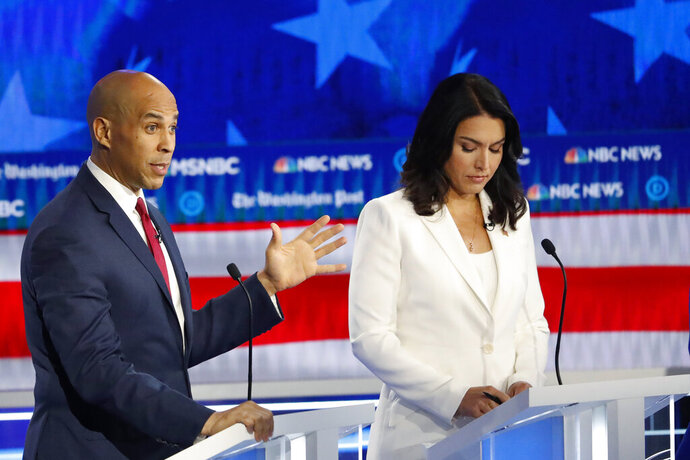 Democratic presidential candidate Sen. Cory Booker, D-N.J., speaks as Rep. Tulsi Gabbard, D-Hawaii, listens during a Democratic presidential primary debate, Wednesday, Nov. 20, 2019, in Atlanta. (AP Photo/John Bazemore)