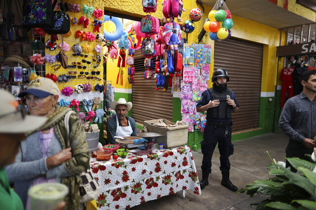FILE - In this Feb. 10, 2020 file photo, a policeman stands guard as the city mayor attends an event to inaugurate renovated sections of the market, which, along with other local businesses, has suffered as violence has kept regional shoppers away in Apaseo El Alto, Guanajuato state, Mexico. The two most powerful drug cartels in the hemisphere are battling over this industrial and farming hub of central Mexico — a state that has attracted gangs for the same reason it has lured auto manufacturers: road and rail networks that lead straight to the U.S. border. (AP Photo/Rebecca Blackwell, File)